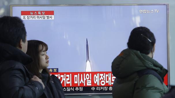 South Koreans watch a TV news programme about North Korea's rocket launch (AP)