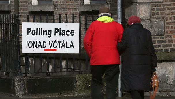 Members of the public walk past a polling station sign in Dublin