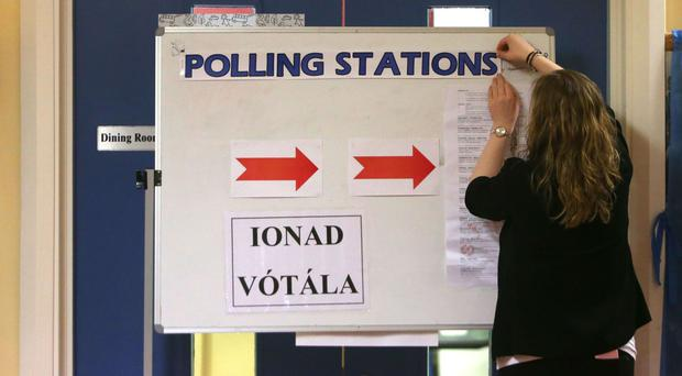 A returning officer adjusts a sign at a polling station at St Anthony's School in Castlebar, Mayo