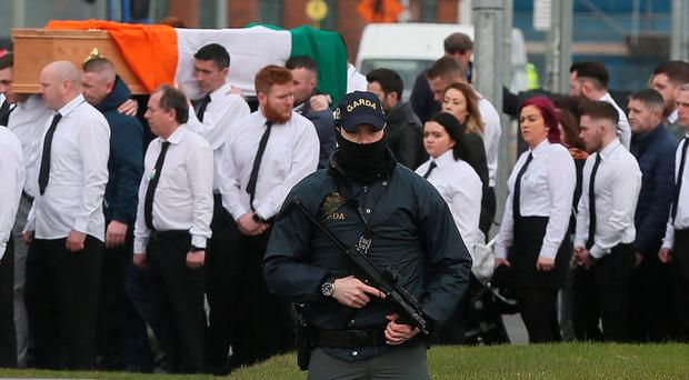 An armed officer looks on as the coffin of Vincent Ryan is carried into church by his brothers