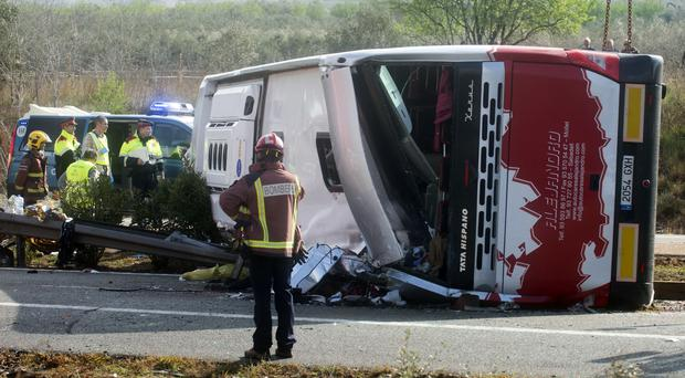 Emergency services personnel stand at the scene of a bus accident near Freginals
