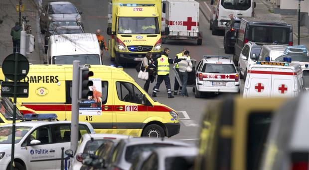 Emergency services evacuate a woman after a explosion in a main metro station in Brussels (AP)