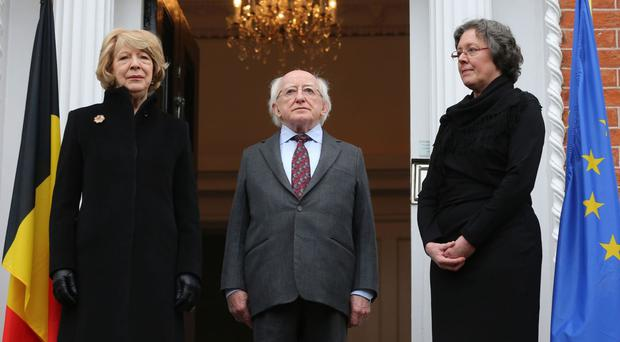 Michael D Higgins and his wife Sabina, left, stand for a minute's silence with deputy head of mission Agnes Schreers outside the Belgian Embassy in Dublin