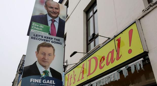 Campaign posters for Fianna Fail leader Micheal Martin, top, and Fine Gael leader Enda Kenny
