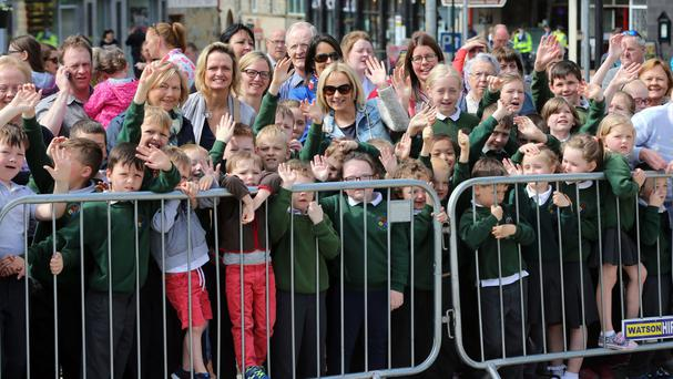 School children await the arrival of the Prince of Wales and the Duchess of Cornwall