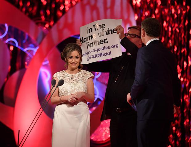 A Fathers4Justice protester dressed as a priest storms the stage as Cavan Rose Lisa Reilly is interviewed in Tralee, before being removed by security men