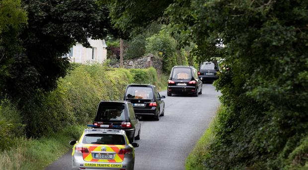 The hearses and a Garda car leave the scene of the tragedy in Ballyjamesduff