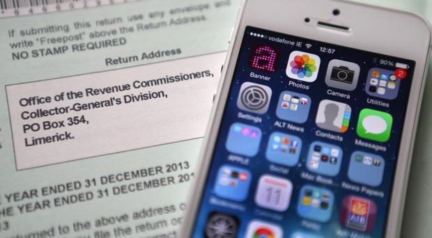 An Apple iPhone beside a tax return form as the tech giant faces a huge tax bill following an EU probe into its 'sweetheart deal' with the Government