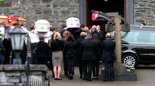Coffins are taken into St Mary's Church in Castlerahan, Co Cavan, where the funeral of the Hawe family took place