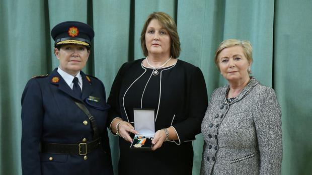 Adrian Donohoe's widow Caroline, centre, receives his Scott Medal for bravery from Garda chief Noirin O'Sullivan and Justice Minister Francis Fitzgerald