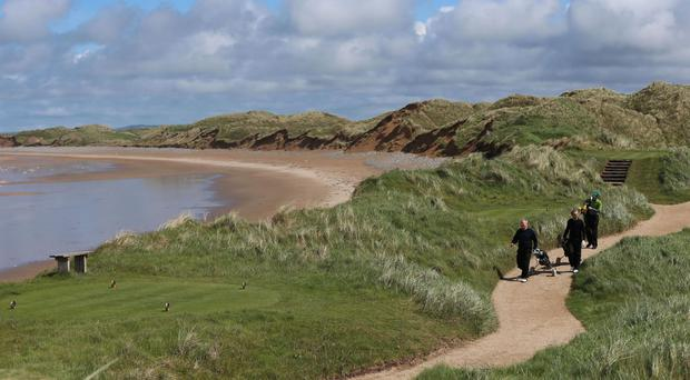 Golfers walk along the coastal path on the Doonbeg Golf Links course and hotel in Co Clare