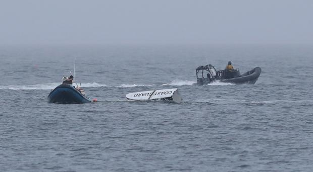 A piece of debris is towed in as the search continues for an Irish Coast Guard helicopter