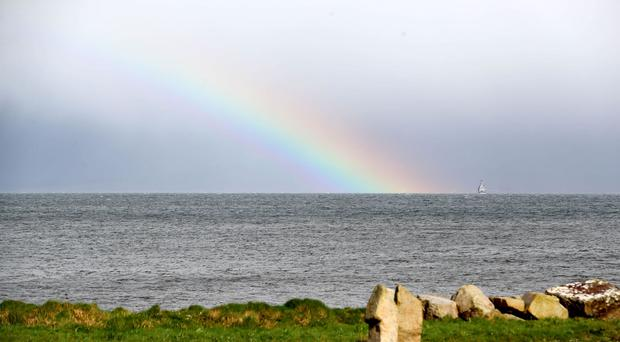 A rainbow displays next to the Irish Naval Service vessel LE Eithne during bad weather in Blacksod Bay, Co Mayo, as the search continues