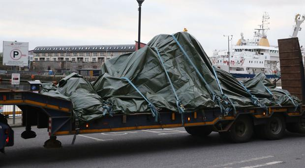 The wreckage of the Irish Coast Guard helicopter is carried on a flat bed truck