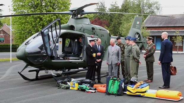 The Prince of Wales is shown an EC 135 rescue helicopter by Vice Admiral Mark Mellett (left) as he visits The Irish Defence Forces/UN Training School at Curragh, in the Republic of Ireland.