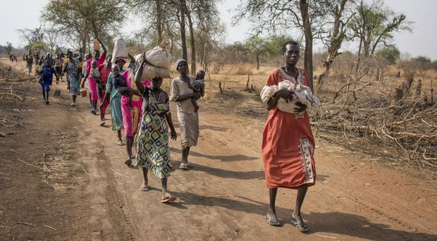 People walk to reach a food distribution site in Malualkuel, in the Northern Bahr el Ghazal region of South Sudan (AP)