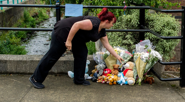 A woman lays flowers outside the apartment where the child died