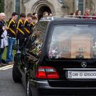 Members of Naomh Ultan GAA club form a guard of honour at the funeral of Margaret McGonagle and her daughter Mairead Mundy