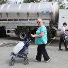 People collect water from a Northern Ireland Water Tanker outside Termonfeckin national school, Drogheda, after a pipe burst.