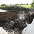 A man looks at a tractor which has fallen into a river after a road collapsed in Iskaheen, County Donegal, after heavy rain left a trail of destruction