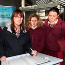 School principal Aedin Ni Bhriain with students Kristina O'Brien, Ciara Deegan and Sophie O'Callaghan sign a book of condolence