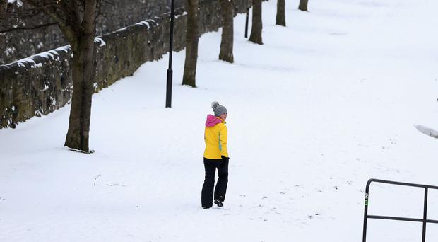A woman walks along the banks of the Royal Canal in Drumcondra, Dublin as the severe weather conditions continue (Brian Lawless/PA)