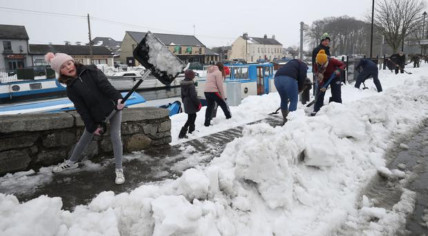 Locals in clean up in the town of Sallins, Co Kildare (Niall Carson/PA)