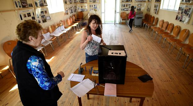 Presiding Officer Carmel McBride looks on as a voter casts their vote on the island of Inishbofin (Clodagh Kilcoyne/PA)