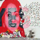 A woman kneels in front of a mural of Savita Halappanavar in Dublin (Niall Carson/PA)