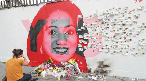 A woman kneels infront of a mural of Savita Halappanavar in Dublin (Niall Carson/PA)
