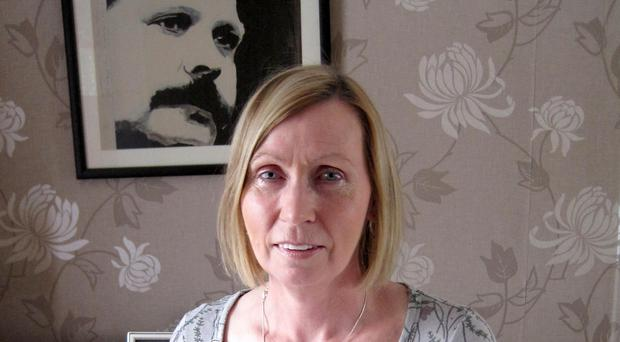 Linda Ervine, who gained an A grade in A-level Irish, in front of a painting of former loyalist leader David Ervine at her home in Belfast (Steven McCaffery/PA)