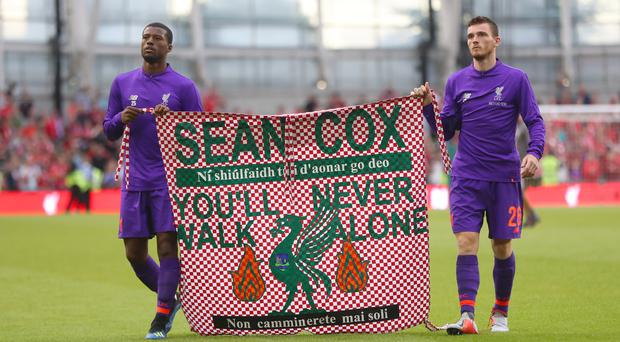 Liverpool's Georginio Wijnaldum (left) and Andy Robertson hold a banner for Liverpool fan Sean Cox (Niall Carson/PA)