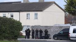 Armed police at the scene where a man has been arrested after a day-long incident in Ronanstown area of Dublin (Niall Carson/PA)