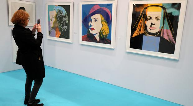 A woman takes a picture of a rare iconic collection of Ingrid Bergman prints by Andy Warhol. The Bergman portfolio consists of 'Herself' (left), 'Bergman with Hat' (centre) and 'Ingrid The Nun' at the Art Source art show at the RDS in Dublin (Brian Lawless/PA)