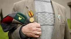 A man wears a War of Independence medal at Arbour Hill cemetery in Dublin (Julien Behal/PA Wire)