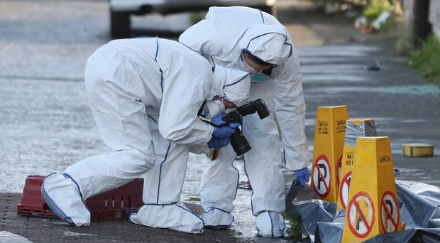 Forensic investigators work at the scene of the shooting in Darndale, Dublin (Brian Lawless/PA)