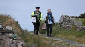 Presiding Officer Carmel McBride and Garda Adrian McGettigan carry the ballot box to the polling station on Inishbofin (Niall Carson/PA)