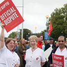 Health support workers Mag Dowling (left) Margaret Doherty (centre) and Naveen Sharma, on strike outside St James's hospital in Dublin (Brian Lawless/PA)