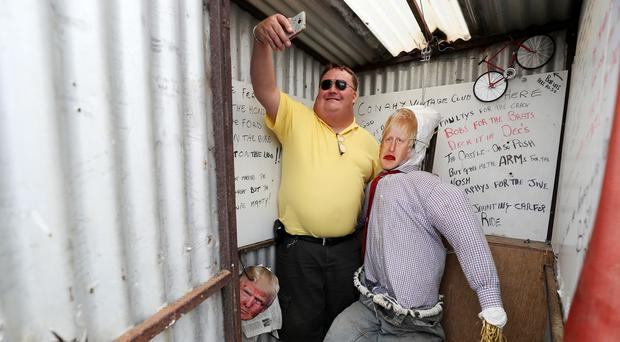 Liam Dermody, from Wicklow, takes a selfie with 'Boris Johnson in a public toilet' at the 10th Durrow Scarecrow Festival, which takes place annually in Durrow, Co. Laois, Ireland (Brian Lawless/PA)