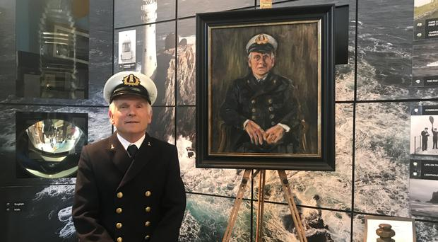 Lightkeeper Gerald Butler, next to the portrait that honours him (Dan Llywelyn Hall/PA)