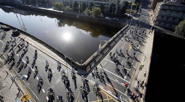 Hundreds of cyclists cross the river Liffey in Dublin (PA)