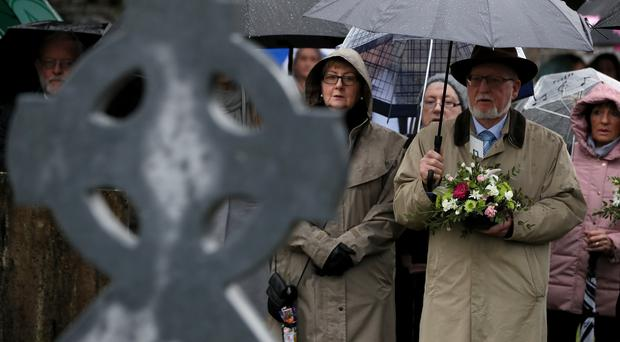 People gather at the grave of Jerome O'Leary during a ceremony at Glasnevin cemetery, Dublin, where the GAA unveiled headstones erected on the unmarked graves of three of the victims of the Bloody Sunday shootings at Croke Park in 1920 (Brian Lawless/PA)