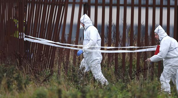 Forensic officers at the scene in the Balbutcher Lane area of Ballymun in north Dublin after a body was found in a container (Niall Carson/PA)