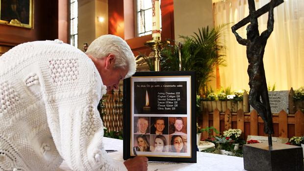 Members of the public sign a book of condolence at the Pro-Cathedral in Dublin's city centre