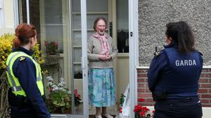 Paula McCadden, from Ballygall, receives her shopping from Community Garda Louise O'Sullivan (right) and probationer Garda Anna Szczepan (PA)
