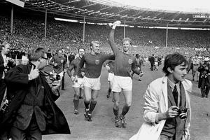 Jack Charlton holds the Jules Rimet trophy aloft as he parades it around Wembley following England's 1966 World Cup final victory (PA)