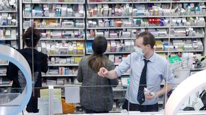 Pharmacists take precautions in the Life Pharmacy in Rathmines, Dublin (Niall Carson/PA)
