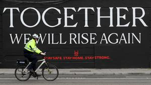 File photo dated 23/04/2020 of a member of An Garda cycling past a mural (PA)