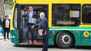 Leo Varadkar and Richard Bruton arrives on a hybrid electric bus (Niall Carson/PA)
