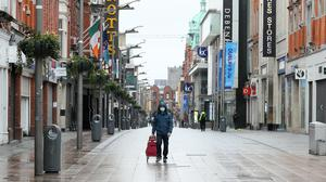 A man walks down an almost deserted Henry Street in Dublin's city centre (Brian Lawless/PA)